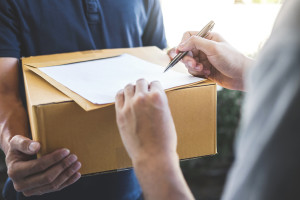 Delivery mail man giving parcel box to recipient and signature form, Young owner signing receipt of delivery package from post shipment courier, Home delivery service and working with service mind.