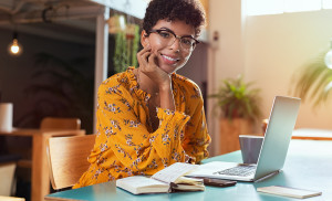 Happy brazilian girl with eyewear in coworking office with laptop looking at camera. Smiling african american student using computer at cafeteria. Successful young stylish business woman with glasses.