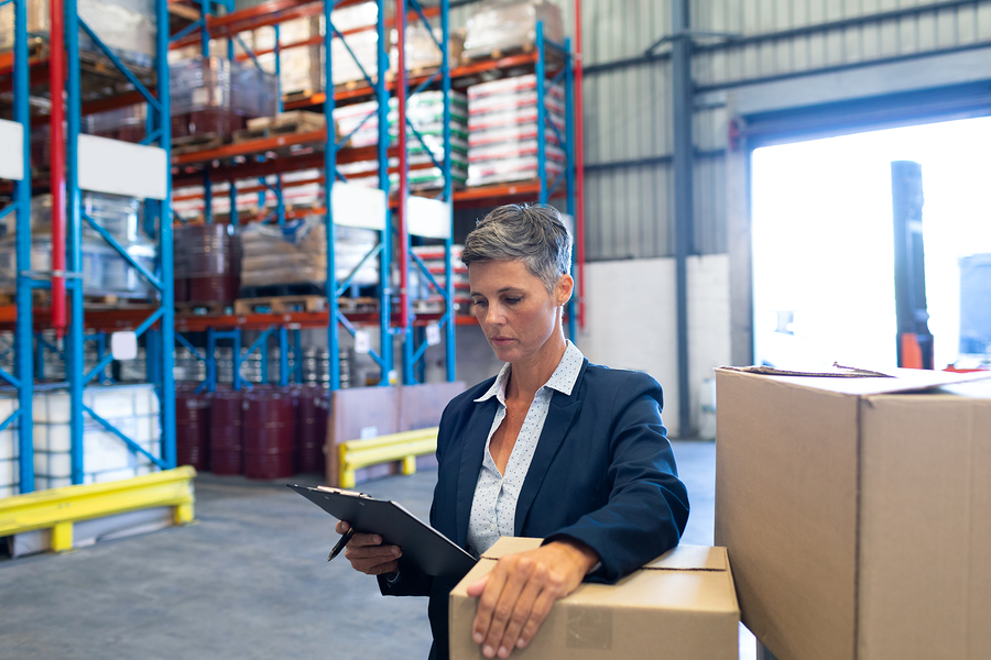 Front view of beautiful mature Caucasian female manager checking stocks on clipboard in warehouse. This is a freight transportation and distribution warehouse. Industrial and industrial workers