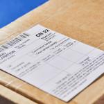 Parcel with Customs declaration form CN22 on a blue velvet background. Close-up