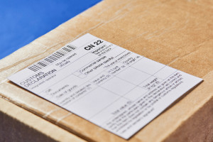Parcel with Customs declaration form CN22 on a blue velvet background. Close-up